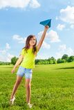 7 years old girl with paper plane. Cute little 7 years old girl holding blue paper airplane on bright sunny day royalty free stock images