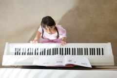 Girl playing piano stock images
