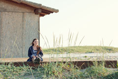 10-years old girl sitting near the wood house. 10-years old smiling girl sitting near the wood house Royalty Free Stock Image