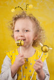 Girl with bee cake pops. 3 years old girl is tasting a bee cake pop stock photography