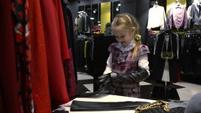 5 years old girl trying on gloves in a clothing store. stock video