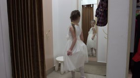 5 years old girl trying on a white dress in a clothing store. stock footage