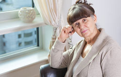 65 years old good looking woman portrait in domestic environment. London Stock Photos