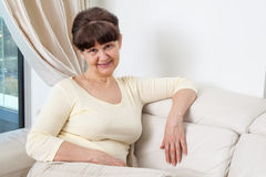 65 years old good looking woman portrait in domestic environment. Royalty Free Stock Photography