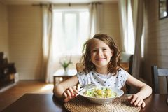 8 years old happy child girl eating pasta at home for lunch Royalty Free Stock Photography