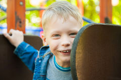 7 years old kid playing at children playground Royalty Free Stock Photos