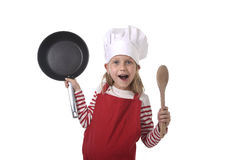 6 or 7 years old little girl in cooking hat and red apron playin Stock Images