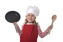 6 or 7 years old little girl in cooking hat and red apron playin Royalty Free Stock Photo