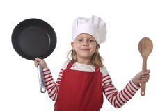 6 or 7 years old little girl in cooking hat and red apron playing cook smiling  happy holding pan and spoon Royalty Free Stock Photo
