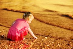 2-3 years old little girl playing with pebbles at the riverbank stock photos