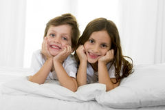 7 years old little girl posing on bed or couch together with her 4 years old small brother smiling happy in brotherhood concept Stock Images