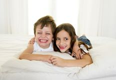 7 years old little girl posing on bed or couch together with her 4 years old small brother smiling happy in brotherhood concept Royalty Free Stock Images