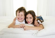 7 years old little girl posing on bed or couch together with her 4 years old small brother smiling happy in brotherhood concept Stock Image