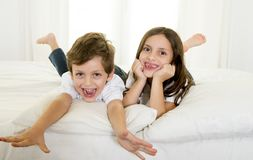 7 years old little girl posing on bed or couch together with her 4 years old small brother smiling happy in brotherhood concept Royalty Free Stock Photos