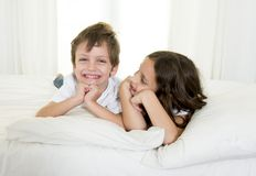 7 years old little girl posing on bed or couch together with her 4 years old small brother smiling happy in brotherhood concept Stock Photo