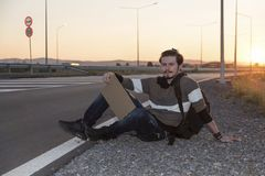 21 years old man sitting on the ground and hitchhiking Royalty Free Stock Photography