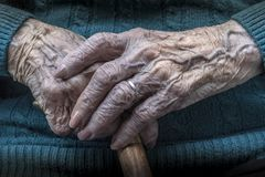 Elderly female hands manicure and cane Royalty Free Stock Images