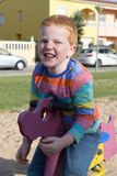 5 years old redheaded happy boy sitting on a seesaw and smiling royalty free stock image