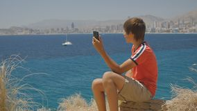 15-years-old teen boy in red t-shirt and shorts making smartphone video call on sea coast city skyline background. 15-years-old teen boy in red t-shirt and stock video footage