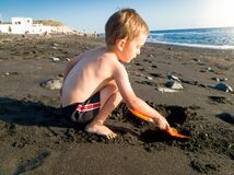 Cute 4 years old toddler boy sitting on the ocean beach and playing with black volcanic sand