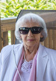 83 years old woman. With sunglasses on chair outdoor stock images