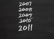 Years passing. Chalkboard or blackboard with dates of previous years crossed off and 2011 shown as the current year stock illustration