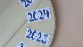 Years from 2014 to 2024 rotating on wooden board and stopped on 2021 year, new year, time is running
