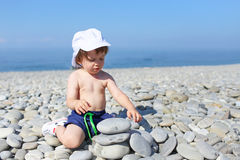 2 years toddler building pebbles tower on the beach Royalty Free Stock Images