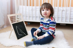 2 years toddler paints on the blackboard Royalty Free Stock Photography