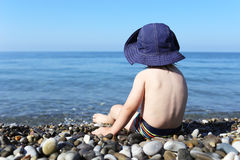 2 years toddler sits on stone beach Royalty Free Stock Photo