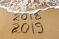 2019, 2018 years written on sandy beach sea. Wave washes awa stock photo