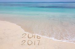 Years 2016 and 2017. Year 2016 is washed away by ocean wave stock photos