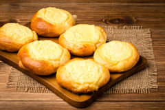 Yeast buns with cheese, traditional russian pastry, on the wooden background. Yeast buns with cheese, traditional russian pastry, on the brown wooden background Stock Photos