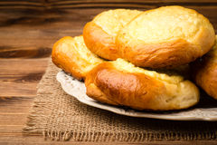 Yeast buns with cheese, traditional russian pastry, on the wooden background. Yeast buns with cheese, traditional russian pastry, on the brown wooden background Royalty Free Stock Photo