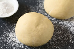 Yeast Dough. Risen or proved yeast dough balls for bread or pizza on a floured slate surface, photographed with natural light Selective Focus, Focus on the front Royalty Free Stock Photo