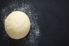 Yeast Dough. Risen or proved yeast dough for bread or pizza on a floured slate surface, photographed overhead with natural light Selective Focus, Focus on the Royalty Free Stock Photography