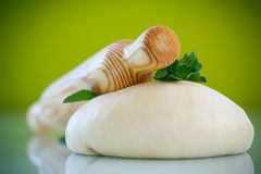 Yeast dough with a wooden rolling pin Royalty Free Stock Image