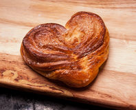 Yeast sweet buns in the shape of a heart on a Board on black baking tray. Country house style. Authentically Royalty Free Stock Image
