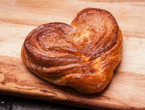 Yeast sweet buns in the shape of a heart on a Board on black baking tray. Country house style. Authentically Stock Image