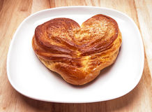 Yeast sweet buns in the shape of a heart and stuffed patties on a dish on an wooden table Royalty Free Stock Photo