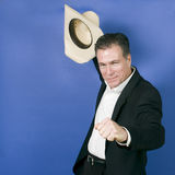 Yeeehaaa!. Mature, handsome, white male wearing a black suite and a white shirt holding a cowboy hat with one hand as if in celebration or exhilaration royalty free stock images