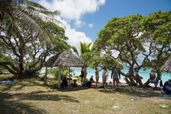 Yejele Beach Party in the Shade. TADINE,MARE,NEW CALEDONIA-DECEMBER 2,2016: Tourists relaxing in the shade under a rustic thatched roof shelter and trees under a Royalty Free Stock Photo