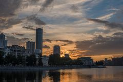 Yekaterinburg city center on sunset. City pond view, amazing clouds and sky. High buildings, skyscrapers on the embankment. Of the river Iset stock image