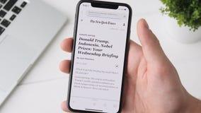 Yekaterinburg Rosja, Październik, - 3, 2018: Mężczyzna gmerania wiadomość o Donald atucie na iPhone X smartphone, wyszukuje zbiory wideo