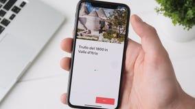 Yekaterinburg, Rusland - Oktober 3, 2018: Mens die Airbnb app op iPhone X gebruiken smartphone, die de pagina doorbladeren stock videobeelden