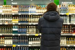 Yekaterinburg, Russia - November 2019. A man in front of the rows of alcohol in the market. The buyer selects the product
