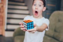 Yekaterinburg Ryssland - mars, 01, 2019 pojken är förvånad och glad som han har fullständigt samlat Rubiks kub arkivbilder