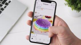 Yekaterinburg Ryssland - Oktober 3, 2018: Man genom att använda Instagram app på smartphonen för iPhone som X bläddrar till och m arkivfilmer