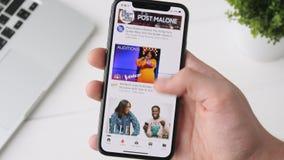 Yekaterinburg Ryssland - Oktober 3, 2018: Man genom att använda Youtube app på smartphonen för iPhone som X bläddrar till och med stock video