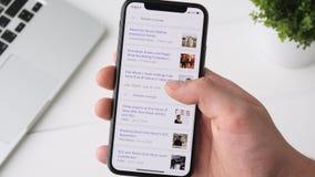 YEKATERINBURG RYSSLAND - OKTOBER 3, 2018: Man sökande av nyheterna om Elon Musk på smartphonen för iPhone som X bläddrar till och lager videofilmer
